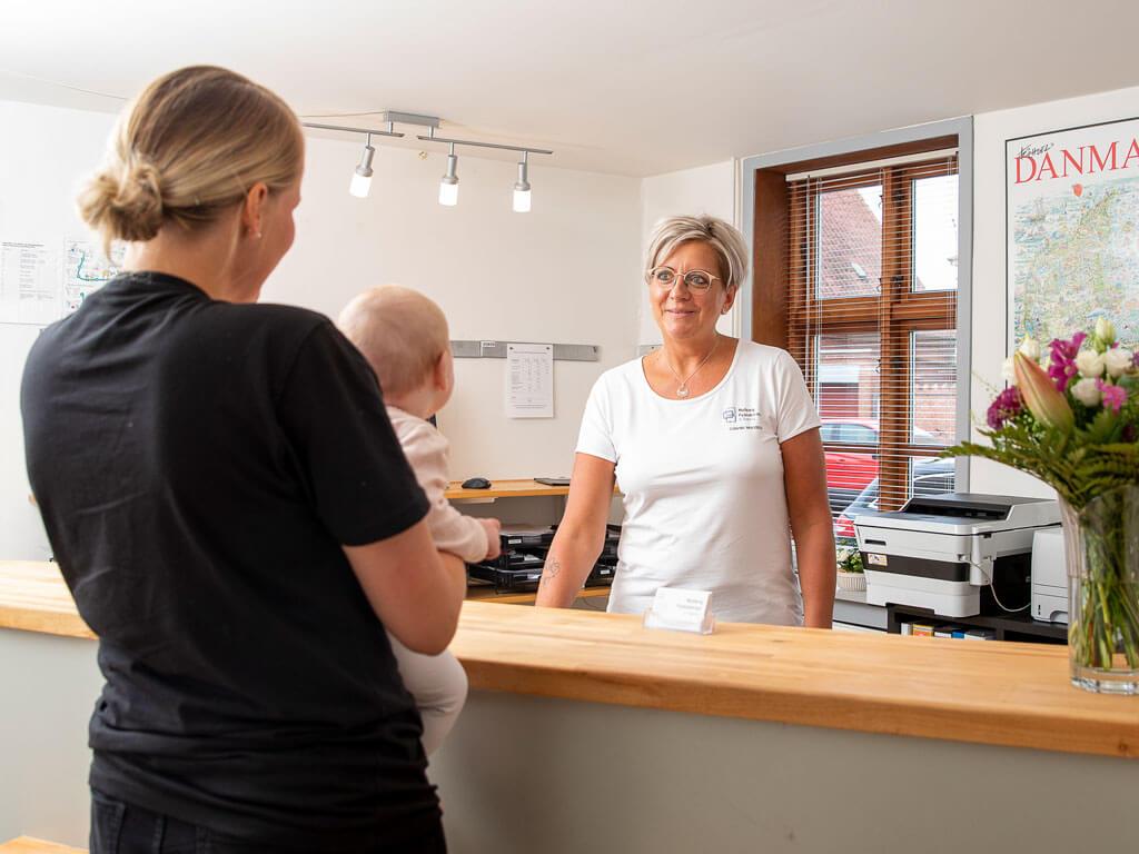 Receptionist Connie byder mor og barn velkommen til Fysioterapeuterne i Nyborg